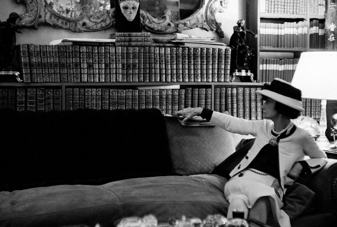 Portret Gabrielle Chanel leżącej na sofie spoglądające na swoją biblioteczkę